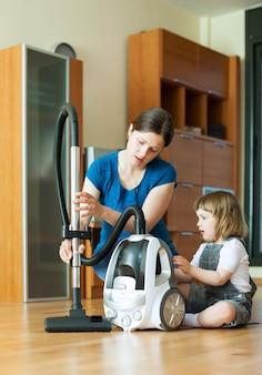 Женщина учит ребенка использовать пылесос