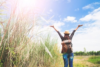 Woman traveler push hands and breathing at field of grasses and blue sky, wanderlust travel concept, space for text