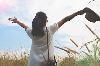 Woman traveler with camera holding hat and breathing at field of yard and forest, wanderlust travel concept, space for text, atmosperic epic moment