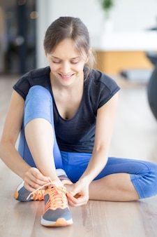 Woman Tying Shoelace and Sitting on Floor in Gym
