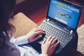 Woman typing in a laptop about last minute flight