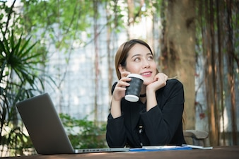 Woman using computer smile coffee
