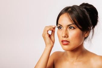 Woman using tweezers on her eyebrows