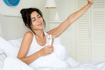 Woman waking up with a glass of water