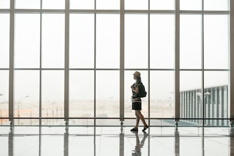 Woman walking in front of a giant glass windows with a hat