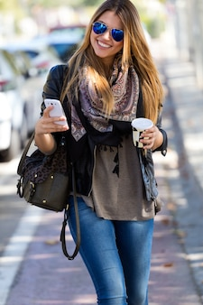 Woman walking with phone and coffee