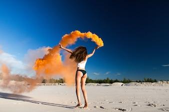Woman walks with orange smoke on white beach under blue sky
