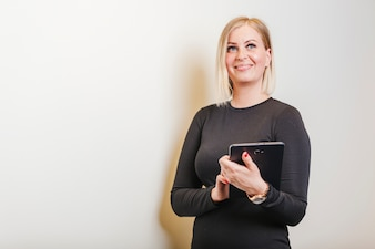 Woman wearing black dress holding tablet smiling