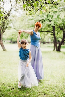 Woman whirls her little daughter posing in the park