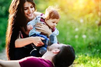 彼女の腕の中で赤ちゃんを持つ女性は、彼女のボーイフレンドは彼女を見ながら、