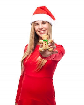 Woman with a cookie person and santa's hat