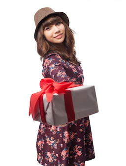 Woman with a gift in a hand and a hat