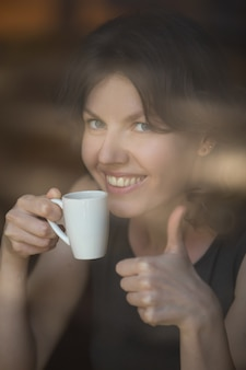Woman with a thumbs up and a coffee