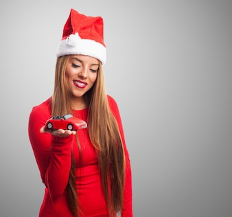 Woman with a toy car and santa's hat