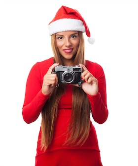 Woman with an old camera and santa's hat