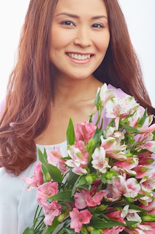 Woman with big smile holding flowers