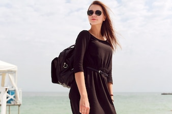 Woman with black dress and sunglasses on the beach