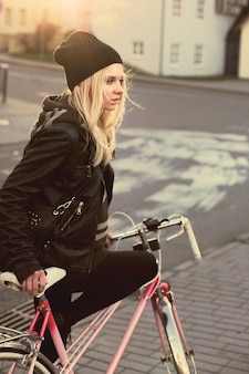 Woman with black jacket sitting on bicycle