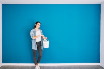 Woman with bucket in front of wall