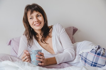 Woman with coffee on bed close up view