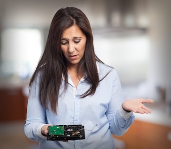 Woman with confused face looking at a hard disk