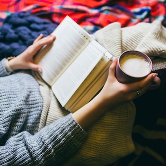 Woman with cup of coffee and book lies under colorful plaids