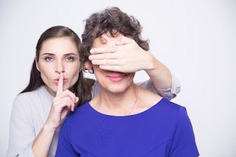 Woman with finger on lips covering mothers eyes