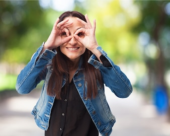 Woman with glasses made with her fingers