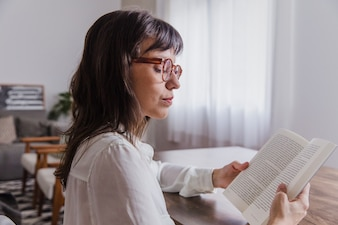 Woman with glasses reading side view