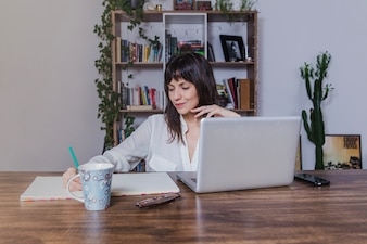Woman with laptop writing