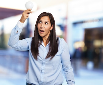 Woman with open mouth and holding a light bulb
