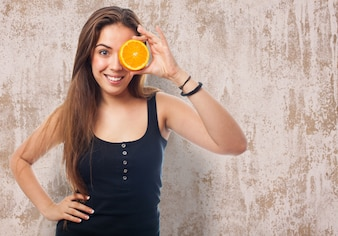 Woman with orange half in one eye