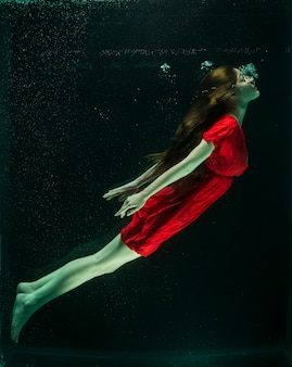 Woman with red dress under water