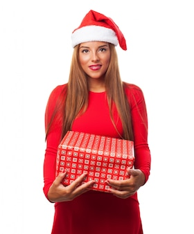 Woman with santa hat and a gift in her hands