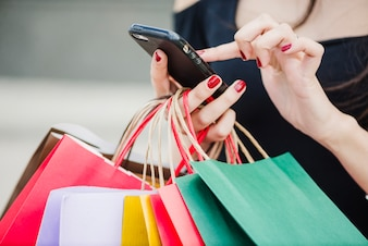 Woman with shopping bags holding smartphone