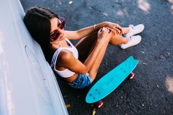 Woman with skateboard leaning on car