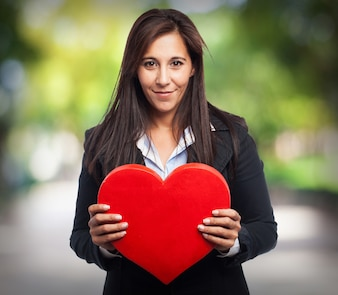 Woman with suit and a heart in hands