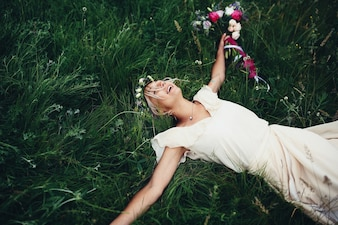 Woman with wedding dress lying on the lawn