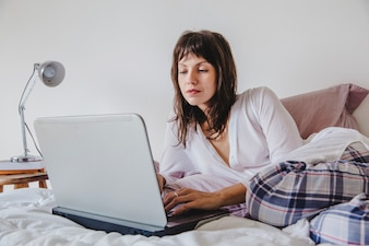 Woman working on laptop on bed