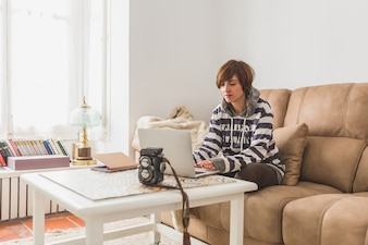 Woman working with the laptop in the living room of her house