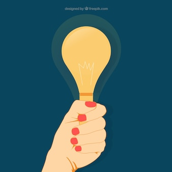 womans hand holding a light bulb