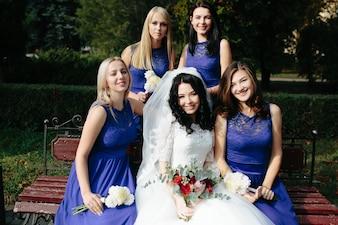 Women in similar dresses posing with bride