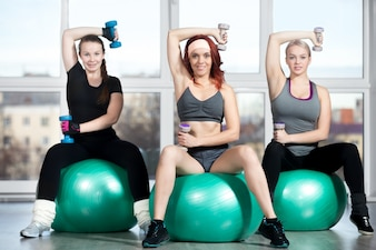Women lifting weigths on a ball