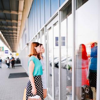 Women looking at dummies behind shop-window