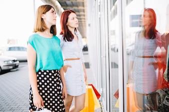 Women looking at goods behind shop-window