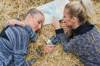 Women lying in hay with map