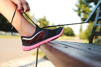 Women's leg with sports shoes on a park bench