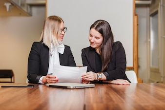Women sitting at table checking documents