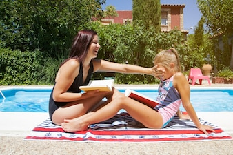 Women with books sitting by pool