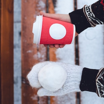 Womn holds snow ball on hand in white glove and red paper cup in another one